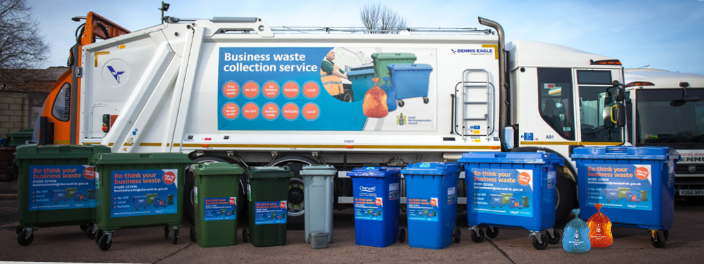 Blue and black waste bins lined up in front of a rubbish lorry