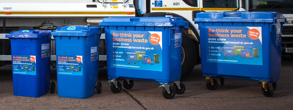 Four blue mixed recycling bins in a row