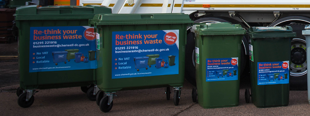 Green recycling bins lined up by biggest to smallest